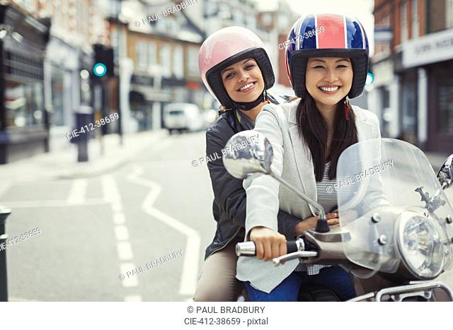 Smiling young women friends wearing helmets, riding motor scooter on urban street