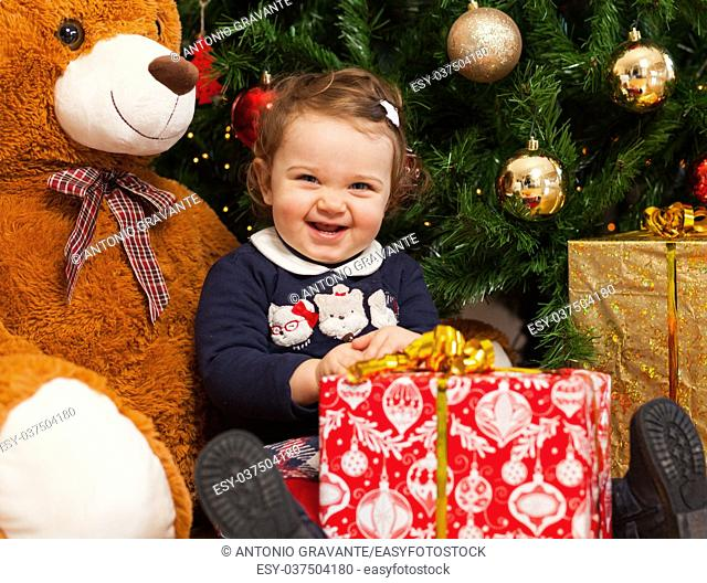 Beautiful toddler baby girl with gifts near christmas tree