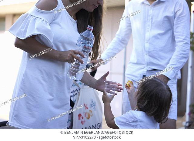 mother with water bottle refilling plastic cub of daughter