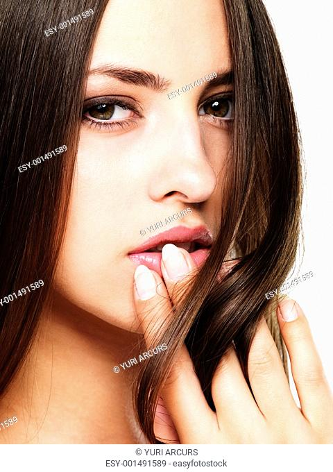 Closeup portrait of pretty woman with fingers on her lips over white background