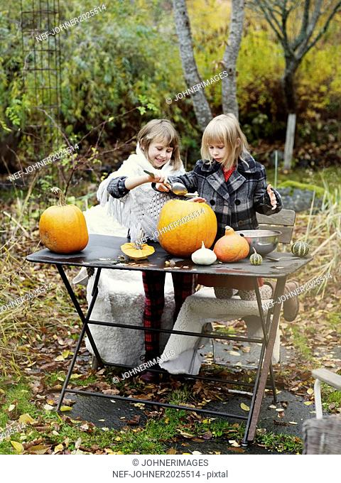 Girls preparing pumpkins