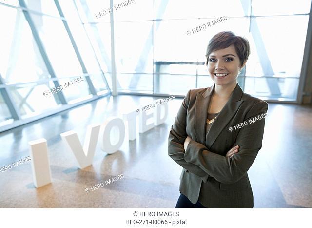 Portrait confident young businesswoman near I Voted text