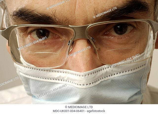 Facial close-up of a dental surgeon wearing a surgical mask and protective glasses