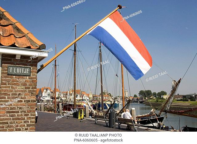 Dutch flag flying from building in New Harbour at Zierikzee, Zeeland, the Netherlands
