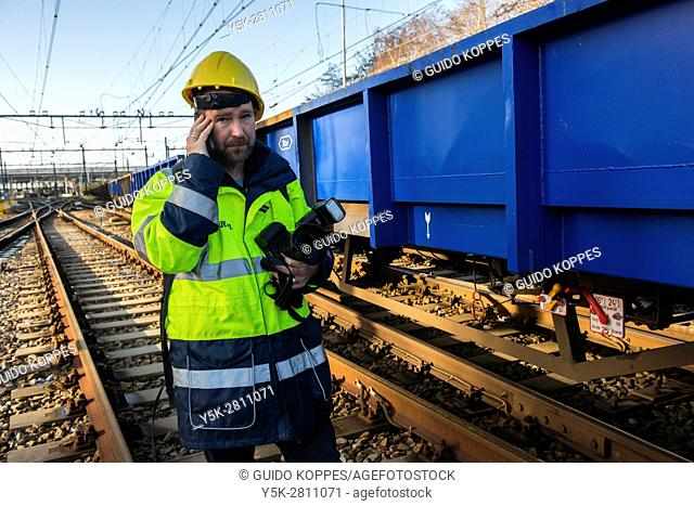 Rotterdam, Netherlands. Male spokesman of ProRail railway infrastructure corporation checking up on major overhaul of a railroad track inside the...
