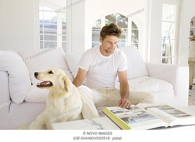 Mid-Adult Man Reading Large Book in Living Room while Petting Pet Dog I