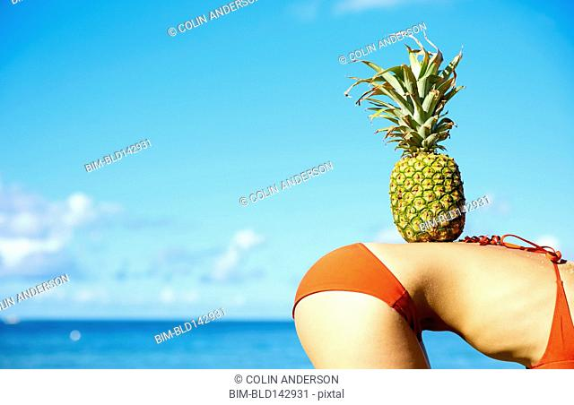 Pacific Islander woman balancing pineapple on back