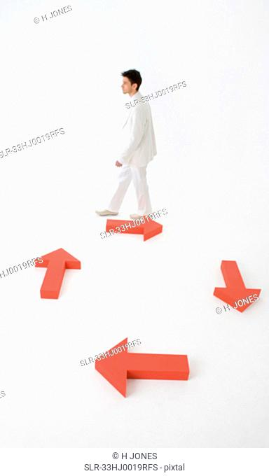 Man walking against directional arrows