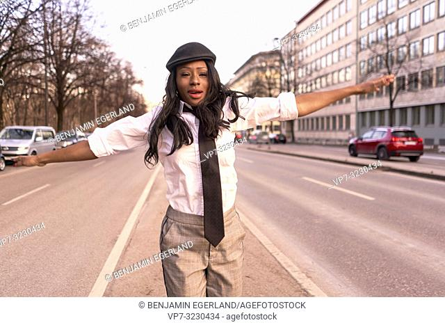 stylish woman jumping in evening sunlight at street, closed eyes, joy, wearing retro business outfit, individual look, African Angolan descent, in city Munich