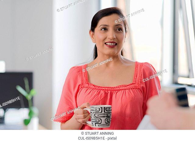 Woman talking to colleague on coffee break