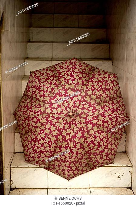 Old red open umbrella on steps