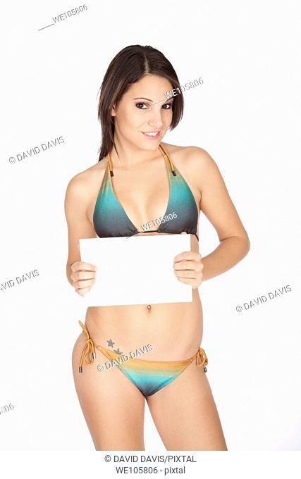 Sexy Caucasian woman wearing a bikini and holding a blank sign