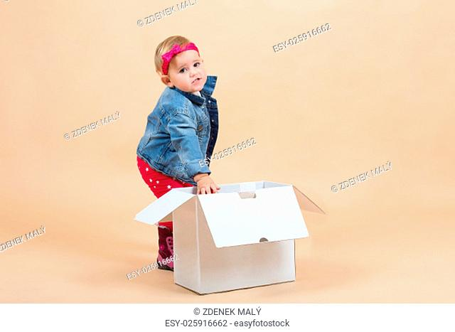 portrait of young cute baby on beige background with white paper box