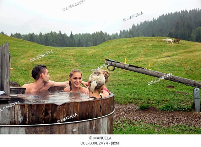 Four adult friends relaxing in rural hot tub, Sattelbergalm, Tyrol, Austria