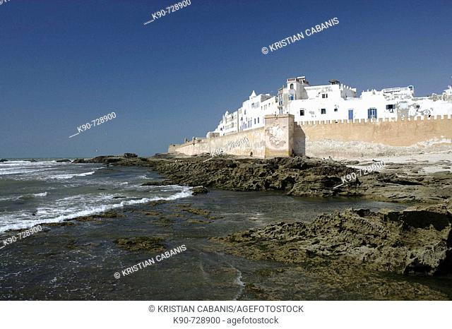 View of the impressive portugese fortification of Essaouira with the surf of the Atlantic Ocean and the white washed buildings and blue doors and window frames...