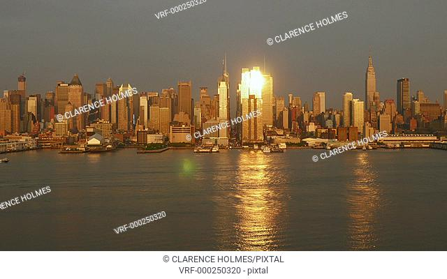 (Time-lapse) The city transitions through sunset into early twilight as the lights of the mid-town Manhattan skyline illuminate behind the Hudson River in New...