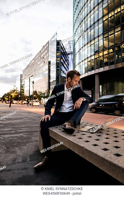 Germany, Berlin, Potsdamer Platz, businessman sitting on bench using laptop in the evening