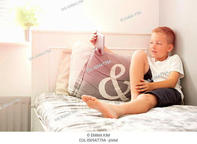 Boy sitting on bed holding digital tablet looking away