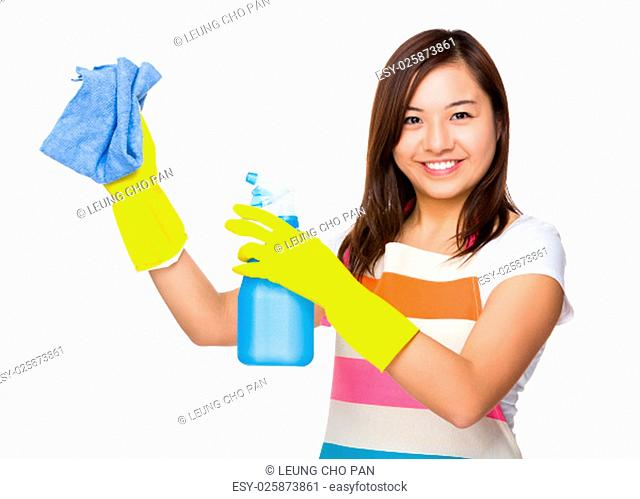 Asian housewife using the spray and rag