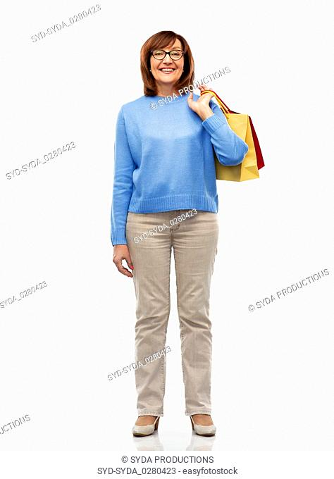 senior woman with shopping bags isolated on white