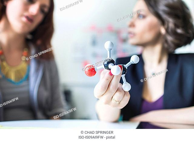 Young women discussing molecular model of Ethanol molecule