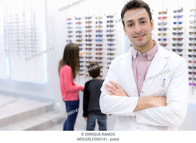 Portrait of smiling optician in shop with people in background