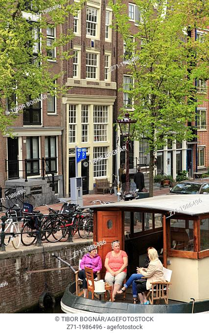 Netherlands, Amsterdam, canal scene, people on a boat,
