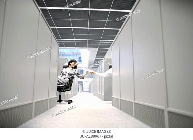 Businesswoman handing something across cubicle hallway