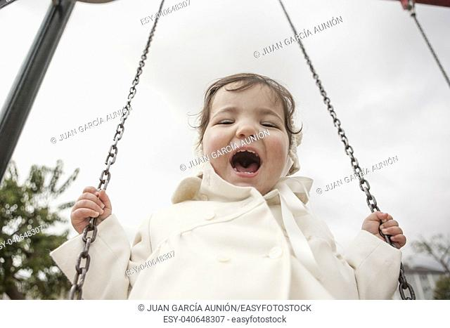 Happy 2 year old girl having fun on a swing on winter. Selective focus
