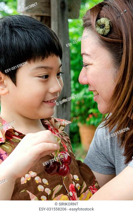 Asian mother with her son cherry on hand
