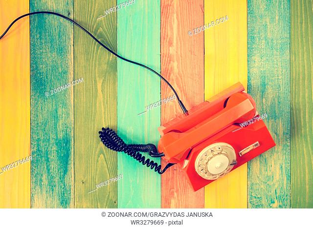 Orange rotary phone on colorful wooden background. Top view