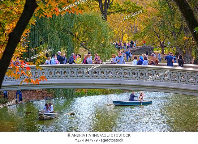Visitors taking in the sights from the Bow Bridge in Central Park, New York, USA