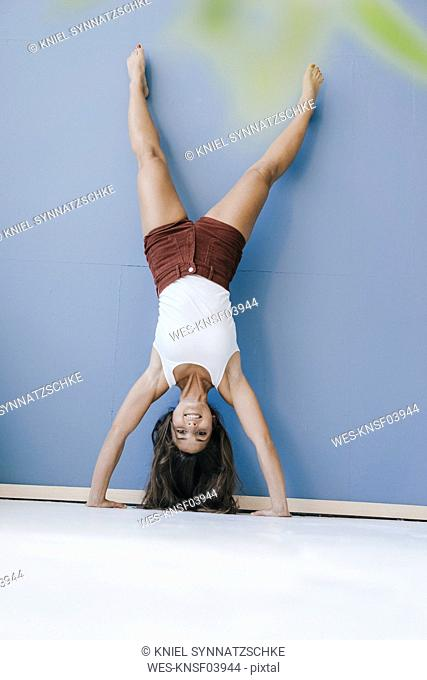Young woman doing handstand against wall