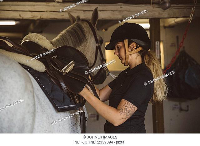 Woman preparing horse for ride