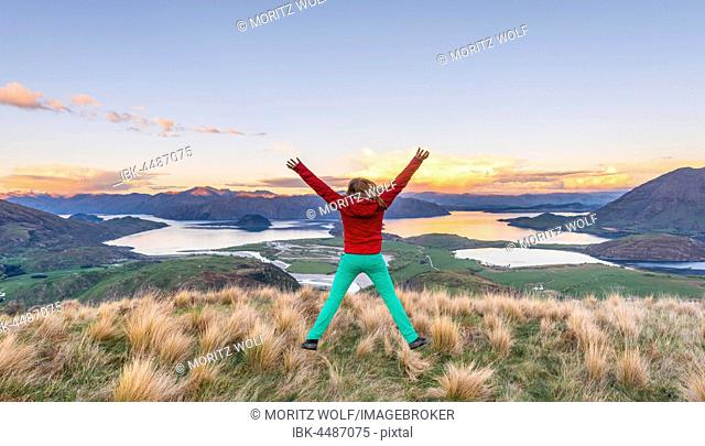 Hiker jumping with limbs spread out in the air, view of Lake Wanaka and mountains, sunset, Rocky Peak, Glendhu Bay, Otago, Southland, New Zealand