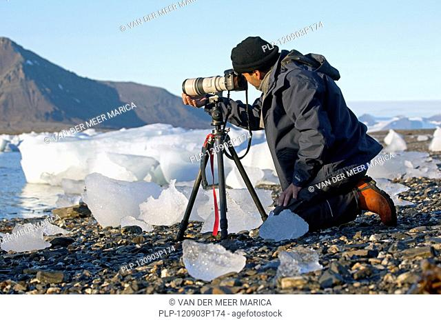Photographer taking pictures with long lens on tripod at Svalbard, Spitsbergen, Norway