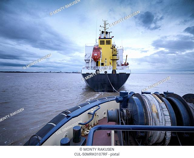 Tugboat towing ship out to sea