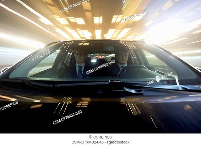 Two businessmen in a car, driving through a tunnel, seen from the hood of the car