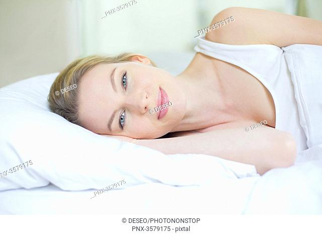 Portrait of a pretty blonde woman in bed looking at camera