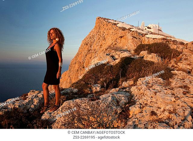 Woman standing at the cliff near the Panagia Kimissis church, Folegandros, Cyclades Islands, Greek Islands, Greece, Europe