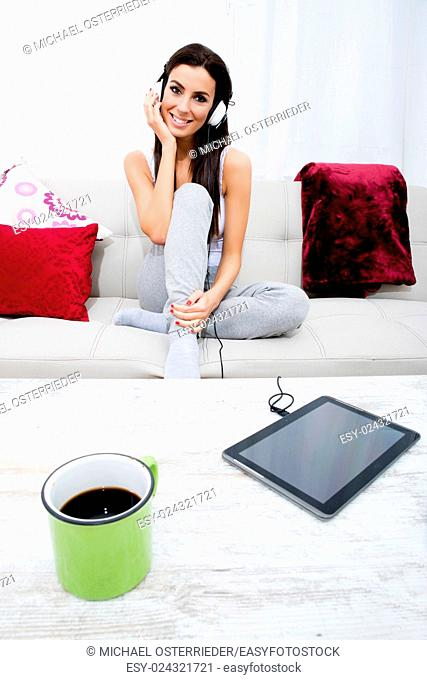Young beautiful woman listening to music with headphones and a Tablet PC at home