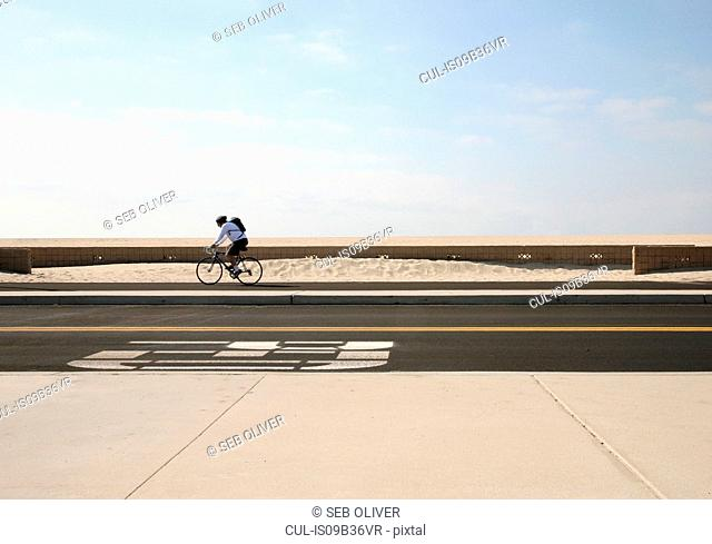 Young man cycling along beach sidewalk, California, USA