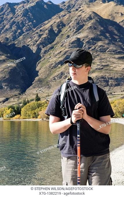 Young hiker resting at Glendhu Bay on the shores of Lake Wanaka, South Island of New Zealand