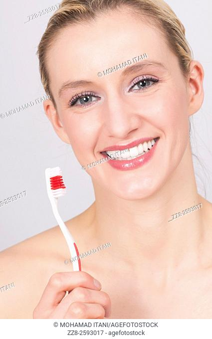 Young woman brushing her teeth with toothbrush