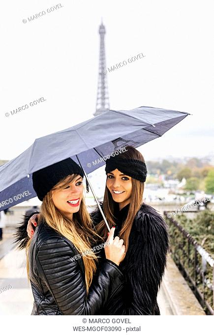 France, Paris, two young women wholding umbrella with the Eiffel Tower in the background