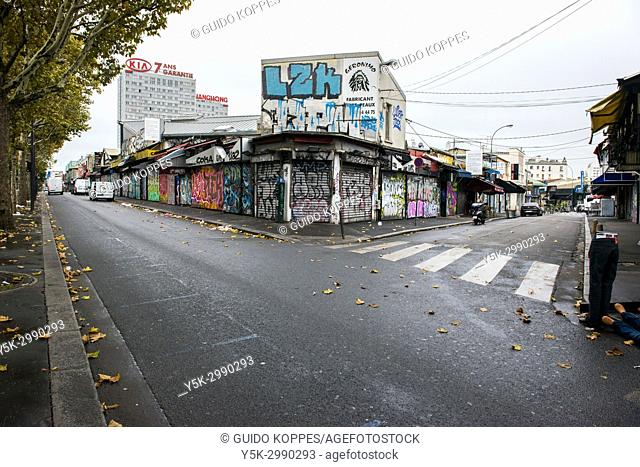 Paris, France. Closed Shops, Stores and Commercial Buildings with blinds shut and street-art. Shops in this district generally open at noon ad attract visitors...