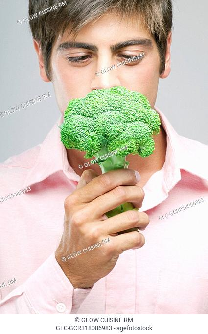 Close-up of a man smelling a broccoli