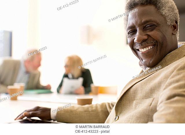 Portrait smiling, confident senior businessman in conference room meeting