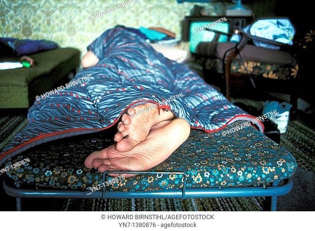 close up of the bare feet of a sleeper in a camp bed in the spare room