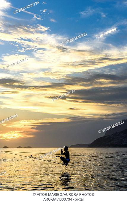 A Man Crouching On A Slackline At Arpoador Beach During The Sunset, Rio De Janeiro, Brazil